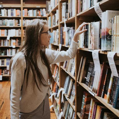 lady choosing a book at a bookstore